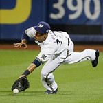 National League's Carlos Gomez, of the Milwaukee Brewers, dives to reach a triple by American League's Prince Fielder, of the Detroit Tigers, during the ninth inning of the MLB All-Star  …