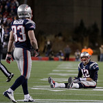 New England Patriots quarterback Tom Brady sits on the field after getting hit during the second half of the NFL football AFC Championship football game against the Baltimore Ravens in Foxb …