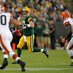 Green Bay Packers quarterback Aaron Rodgers scrambles while being rushed by Cleveland Browns' L.J. Fort (40) and  James-Michael Johnson (50) during the first half of a preseason NFL football …