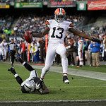 Cleveland Browns wide receiver Josh Gordon (13) scores on a 44-yard touchdown reception in front of Oakland Raiders defensive back Ron Bartell (21) during the second quarter of an NFL footba …