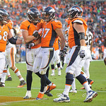 Denver Broncos wide receiver Eric Decker (87) is congratulated by teammates after scoring on an 8-yard pass reception against Cleveland Browns in the third quarter of an NFL football game, S …