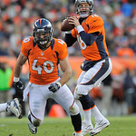 Denver Broncos quarterback Peyton Manning (18) looks for a reciever behind the blocking of running back Jacob Hester (40) during the fourth quarter against the Cleveland Browns in a NFL foot …