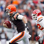 Cleveland Browns quarterback Brandon Weeden runs away from Kansas City Chiefs nose tackle Dontari Poe in the first quarter of an NFL football game in Cleveland, Sunday, Dec. 9, 2012. (AP Pho …
