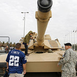 Sergeant Danny York, right, looks on as Bryan Holcome, left, watches as his son Joshua, 8, explores a M1A2 Abrams tank on display before the start of the first half of an NFL football game b …