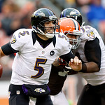 Baltimore Ravens quarterback Joe Flacco (5) scrambles away from the rush by Cleveland Browns defensive end Juqua Parker in the second quarter of an NFL football game in Cleveland, Sunday, No …