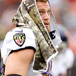 Baltimore Ravens linebacker Paul Kruger watches from the sidelines with a special Salute to Service towel before an NFL football game against the Cleveland Browns in Cleveland, Sunday, Nov. …