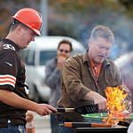 Kevin Vassar of Cincinnati, left, cooks some burgers on the grill while tailgating in front of Cleveland Browns Stadium before an NFL football game between the Cleveland Browns and the Cinci …