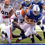 Indianapolis Colts' Andrew Luck goes in for an 3-yard touchdown run against Cleveland Browns' D'Qwell Jackson, left, and Ahtyba Rubin (71)  during the first half of an NFL football game Sund …