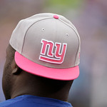 To call attention to Breast Cancer Awareness month, an NFL player wears a hat with the New York Giants logo in pink during the second half of an NFL football game Sunday, Oct. 7, 2012, in Ea …