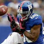 New York Giants wide receiver Victor Cruz (80) fumbles the ball showing the Breast Cancer awareness logo as he is defended by Cleveland Browns cornerback Sheldon Brown and during the second …