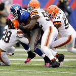 New York Giants running back Ahmad Bradshaw (44) is tackled by Cleveland Browns middle linebacker D'Qwell Jackson (52),  Craig Robertson (53) and  Usama Young (28) during the first half of a …