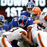 Cleveland Browns strong safety T.J. Ward (43) and John Hughes (93) hit New York Giants running back Ahmad Bradshaw (44) during the first half of an NFL football game Sunday, Oct. 7, 2012, i …