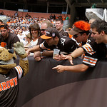 Cleveland Browns fans high-five Chomps, the Browns mascot, during an NFL football game against the Philadelphia Eagles Sunday, Sept. 9, 2012, in Cleveland. (AP Photo/Tony Dejak)