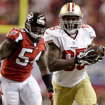 San Francisco 49ers tight end Vernon Davis carries the ball as Atlanta Falcons outside linebacker Stephen Nicholas chases him during the second half of the NFL football NFC Championship game …