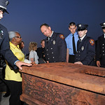 Local fire fighters and residents touch a piece of World Trade Center steel after it was unveiled during the Passaic County 12th Anniversary 9/11 Memorial Ceremony at the Passaic County Publ …