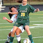Amherst's #20 Lexi O'Connor tries to keep the ball from Avon Lake's #11 Emily Peterson.