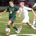 Amherst's #16 Julie Lacock takes the ball past Avon Lake's #7 Claire Jones.