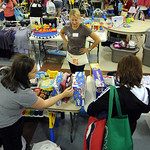 Rory Reding, rear, of Avon, sells resale items at her table at the Kkid's Kloset resale event, by the Avon Early Childhood PtA, at Avon High Sep. 25.  Steve Manheim