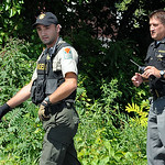 A Lorain County MetroParks Ranger and Lorain County Sheriff's deputy search for evidence after an arrest on July 14. STEVE MANHEIM/CHRONICLE