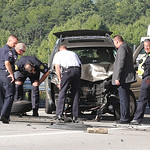 Investigators look over the damaged Jeep at the scene of the accident on I-90 under the Nagel Road overpass.