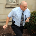 Elyria Police Lt. Andy Eichenlaub runs to his car from Fifth Third Bank on Broad Street in pursuit of a bank robbery suspect on Aug. 9.   Steve Manheim