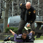 Outside the old Lorain County Courthouse, A Lorain County Sheriff's Deputy prepares to cuff a man who was reported to have a .380 handgun. It turned out to be a Playstation controller that w …
