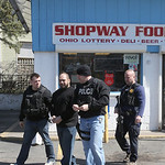 Police officers lead a man away from the Shopway Food Mart in cuffs following a multi-department raid on the business.