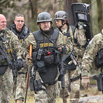 SWAT team members head away from the house on Route 303 in Pittsfield Township where a man held them at bay for most of the day. Officers found him dead of a self-inflicted gunshot wound.