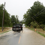 A resident on West Road in Wellington drives across a flooded roadway. the poles on the east side of the road are bent toward the road from storm damage yesterday when a tree came down on th …
