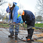 Marvin Shoup, left, and Mike Sigurani, of Blue Jay Communications, work on fiber optic lines on Warden Ave. in Elyria on Oct. 30.   Steve manheim