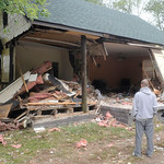 In this Oct. 5, 2010 photo, Leonard Roop, right, and Charles Snow look over damage to a home owned by Roop's son that was caused by a car that crashed into it in Massieville, Ohio, (AP Photo …
