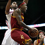 Cleveland Cavaliers guard Daniel Gibson, fornt, goes up for a shot against the defense of Atlanta Hawks forward Marvin Williams, left rear, during the third quarter of an NBA basketball game …