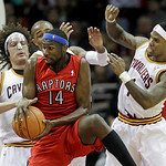 Toronto Raptors' Julian Wright grabs a rebound ahead of Cleveland Cavaliers' Anderson Varejao, left, from Brazil, abd Daniel Gibson, right, in the second quarter in an NBA basketball game We …