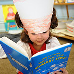Sophia Brown-White, a first grader at McKinley Elementary, reads a Dr. Suess book in Lisa Ward's first grade class at a Dr. Suess birthday celebration on Mar. 2.  Steve Manheim