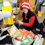 Lisa Ward, first grade teacher, reads with her students, Kamia Pilson, left, and Donovan Wolfe, at a Dr. Suess birthday celebration at McKinley Elementary March 2.  Steve Manheim