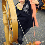 Alexandria Zanda,  11, of Pittsfield Twp., tries her hand aat spinning cridale wool on the child's great wheel, at the Hobby and Activity Day at Amherst Public Library on Apr. 9.  Over 30 bo …
