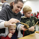 Mary Michael of LaGrange and her boys Liam Michael (3yrs) and Isaac Michael (7yrs) make animal feeders uses peanut butter, pine cones, and seeds. photo by Ray Riedel