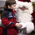 Michael from LaGrange, parents preferred not to give last name , age 7, whispers in Santa's ear at the LaGrange Christmas on the Square. photo by Ray Riedel