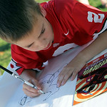 ANNA NORRIS/CHRONICLE Colin Daggett, 9, of Elyria, looks at the cover of his Daredevil comic book for reference as he draws Daredevil onto a large sheet of paper as part of the Superhero Pub …