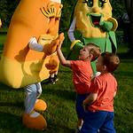 North Ridgeville twins Landen and Caeden Springthorpe, 3, high five and dance with the Corn Festival mascots on Friday.  KRISTIN BAUER | CHRONICLE
