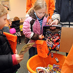 Kylie Klein, 7, center, and sister Samantha, 5, of North Ridgeville, pour Halloween candy into a container at the candy buyback at Dr. Scott Nagy's dental office in Elyria. Steve Manheim