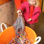 Emma Geiger, 3, of Elyria, pours Halloween candy into a container at the candy buyback at Dr. Scott Nagy's dental office in Elyria. Steve Manheim