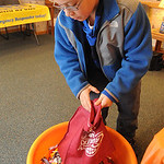 Joshua Vincent, 11, of Elyria, pours  Halloween candy into a container at the candy buyback at Dr. Scott Nagy's dental office in Elyria. Steve Manheim