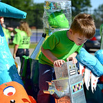 Luke Rainey, 3, of Elyria, investigates the robots and aliens aboard the Elyria High School float on Saturday.  KRISTIN BAUER | CHRONICLE