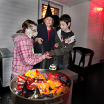 From Left: Samantha Hawkey (as cat) Julie Hawkey (as witch) get candy from Zak Strock and his cauldren of candy on Prospect Street in Elyria. Photo by Tom Mahl