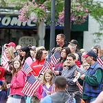 People line the sidewalk along Broad Street waving small American Flags watching the annual Elyria Memorial Day parade in downtown Elyria yesterday morning. (CT photo by Anna Norris.)