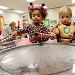 Giraffe Salleena Head, 3, and Ironman Mason Schneider, 3, make music together on a drum during the Halloween events at Elyria Early Childhood Village. The event included an appearance by the …
