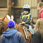 "Dimitry Hruby, age 4 of LaGrange, is helped onto a horse to ride during the Angels Haven ""Hoppin Around the Barn"" fund raising event at Evergreen Farm in Grafton.photo by Ray Riedel"