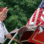 A member of the Al Koran Shriners waves to a crowd as he rides on an antique fire truck. ANNA NORRIS/CHRONICLE