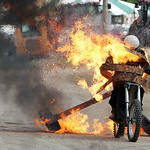 A stunt driver rides a motorcycle through a burning wall during the Black Cat Hell Drivers stunt show at the Lorain County Fair Sunday afternoon in Wellington. ANNA NORRIS/CHRONICLE